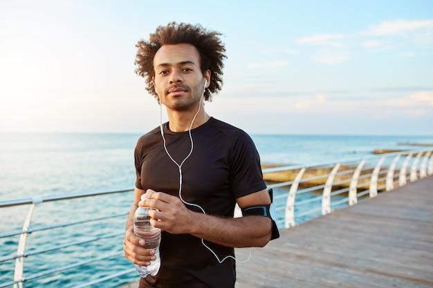 Vrolijke sportman met donkere huid drinkwater uit plastic fles, met oortelefoons die pauze neemt tijdens het joggen. portret van een donkere atleet die van ochtend en muziek geniet.