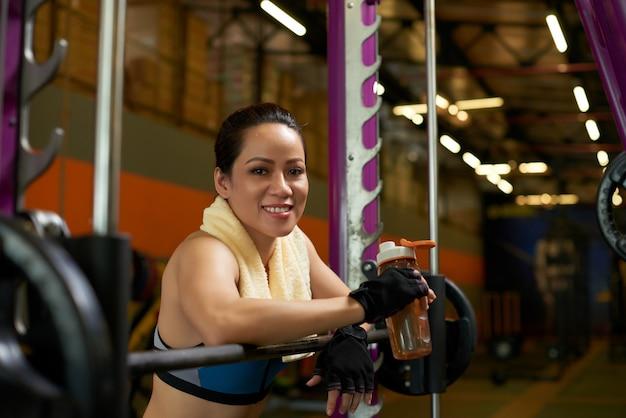 Vrolijke sportvrouw die bij camera bij de smith-machine in een gymnastiek glimlachen