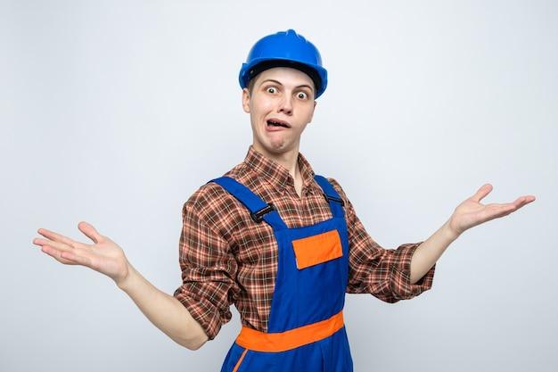 Vrolijke spreidende handen jonge mannelijke bouwer die uniform draagt