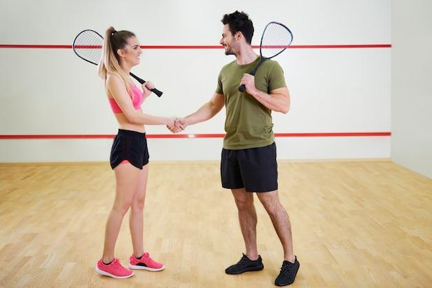 Vrolijke squashspelers schudden elkaar de hand