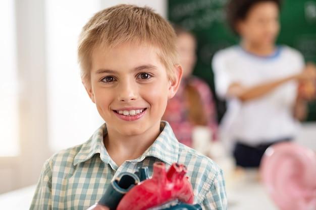 Vrolijke stemming. portret van een opgetogen gelukkige jongen die naar je kijkt terwijl hij een hartmodel vasthoudt