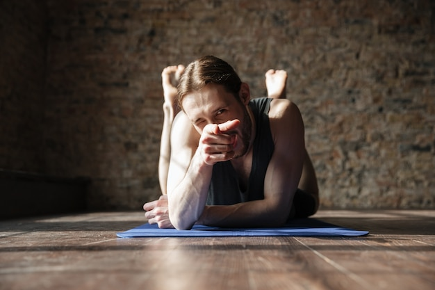 Vrolijke sterke sportman in sportschool ligt op de vloer en wijzen