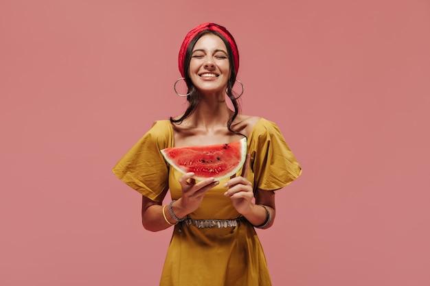 Vrolijke stijlvolle dame met cool kapsel in heldere bandana, zilveren ronde oorbellen en gele zomerjurk poseren met gesloten ogen