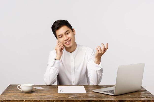 Vrolijke, stijlvolle jonge aziatische mannelijke officemanager iets op de telefoon bespreken, werk zitten met laptop, documenten, koffie drinken, gebaren als praten, persoon bellen om zaken te bespreken