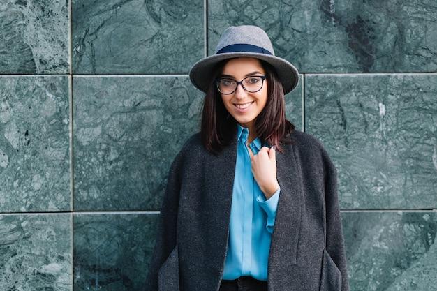 Vrolijke stijlvolle jonge vrouw in grijze hoed, jas, zwarte bril glimlachend en poseren op grijze muur. luxe kleding, modieus model, opgewekte sfeer.