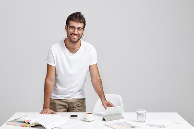 Vrolijke stijlvolle mannelijke freelancer blij met een succesvolle dag