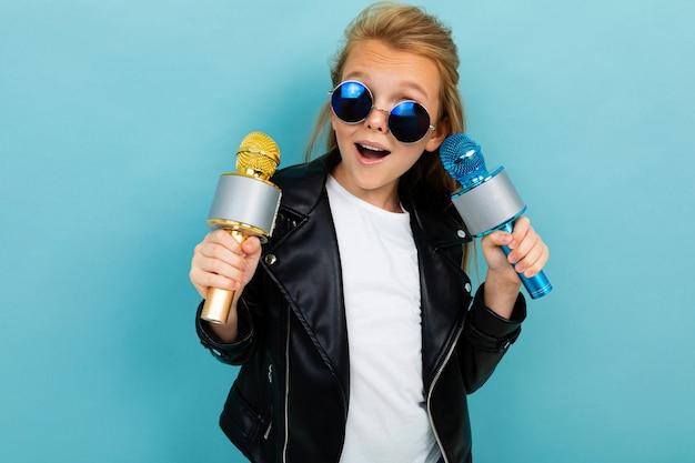 Vrolijke stijlvolle modieus meisje op een blauwe achtergrond met een microfoon in haar handen poseren