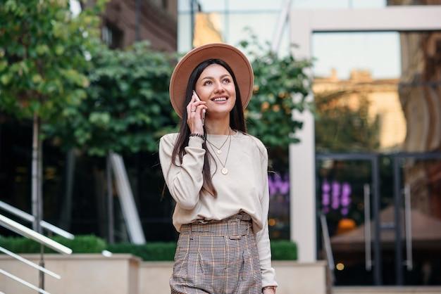 Vrolijke stijlvolle vrouw spreekt op mobiele telefoon in stadsruimte, genietend van buiten wandelen.