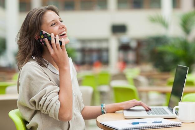 Vrolijke student die cellphone en laptop met behulp van bij cafetarialijst