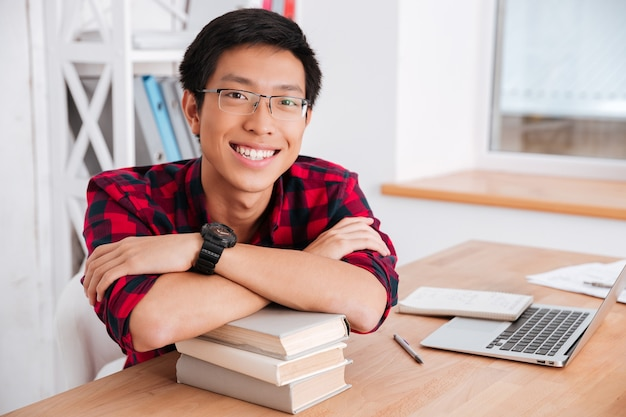 Vrolijke student, gekleed in shirt in een kooi, leunde met de ellebogen op boeken terwijl hij naar voren keek