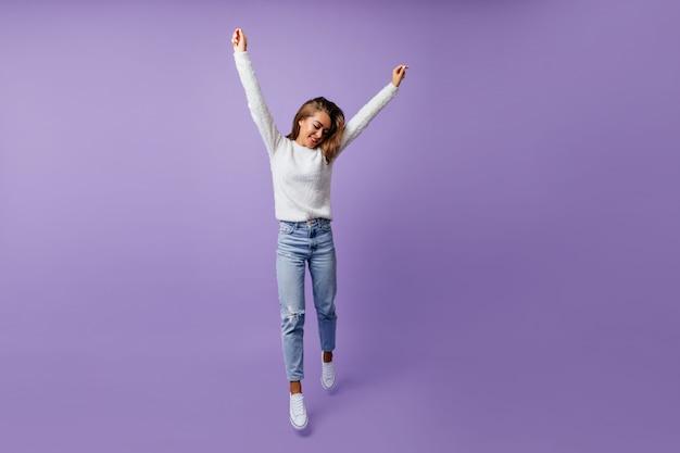 Vrolijke student in goed humeur gelukkig springen. langharige bruinharige vrouw in stijlvolle jeans en witte sneakers vormt voor het portret van volledige lengte