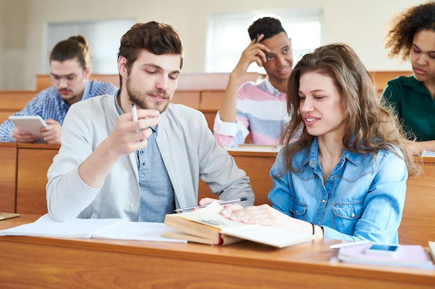 Vrolijke studenten die handboek bespreken bij onderbreking vóór seminarie