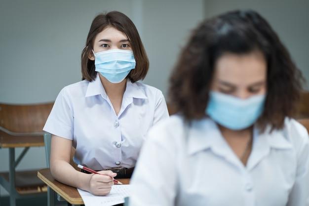 Vrolijke studenten in de klas dragen beschermende gezichtsmaskers en gebruiken antiseptische middelen voor coronaviruspreventie tijdens de pandemie van het coronavirus. groep studenten die beschermingsmaskers dragen in de klas.
