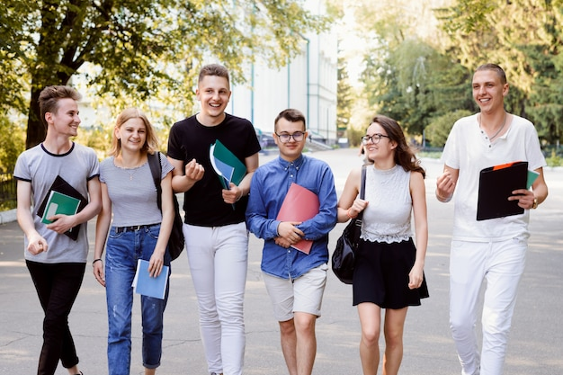 Vrolijke studentenvrienden in het park die communiceren en samen tijd doorbrengen