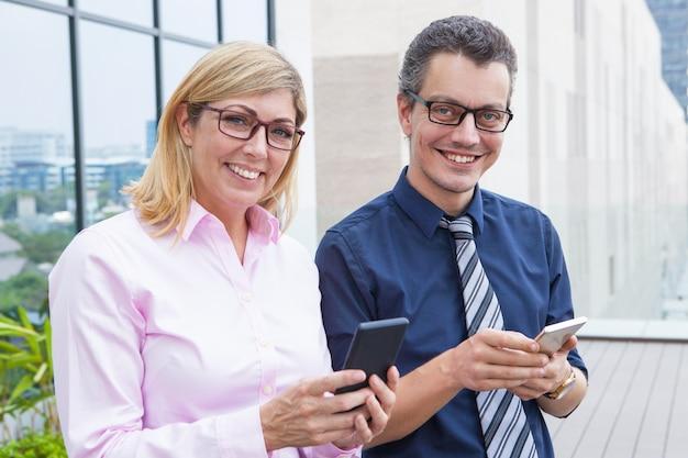 Vrolijke succesvolle bedrijfsmensen die smartphones gebruiken en camera in stad bekijken.