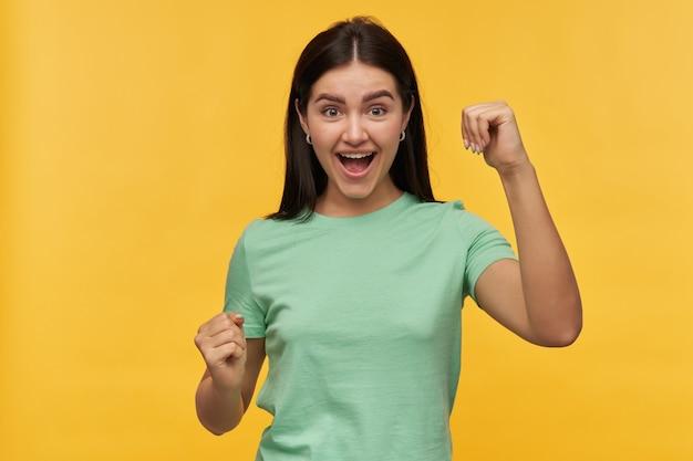 Vrolijke succesvolle brunette jonge vrouw in mint tshirt schreeuwen en vieren overwinning geïsoleerd over gele muur