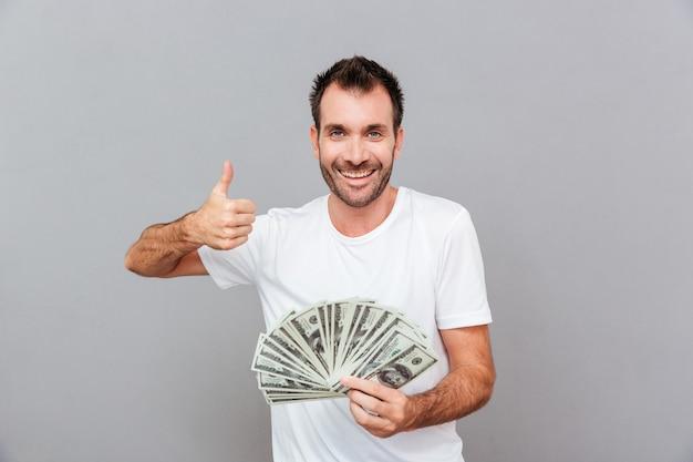 Vrolijke succesvolle jonge man die geld aanhoudt en duimen laat zien over grijze achtergrond