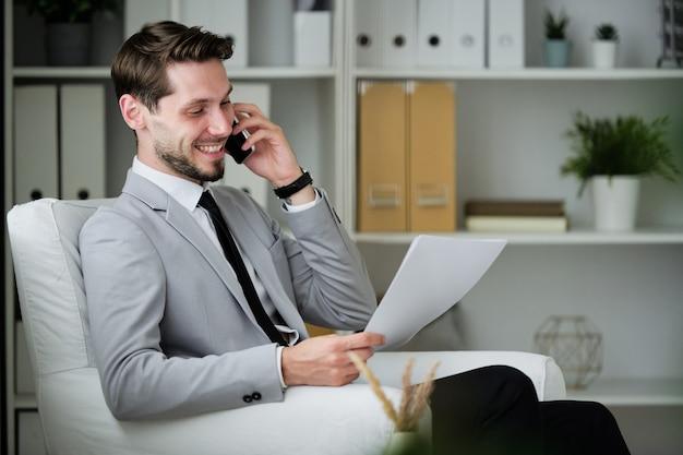 Vrolijke succesvolle jonge zakenman met baard zitten in een comfortabele fauteuil in kantoor en contract bekijken tijdens het communiceren via de telefoon