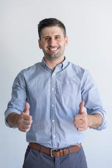Vrolijke succesvolle knappe zakenman met stoppels die duim-omhoog tonen