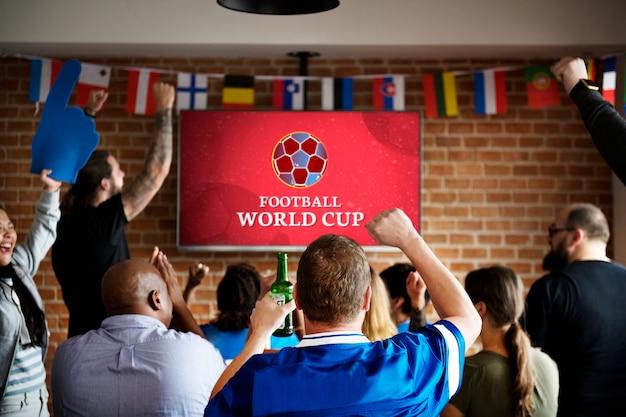 Vrolijke supporters kijken naar voetbal in de pub