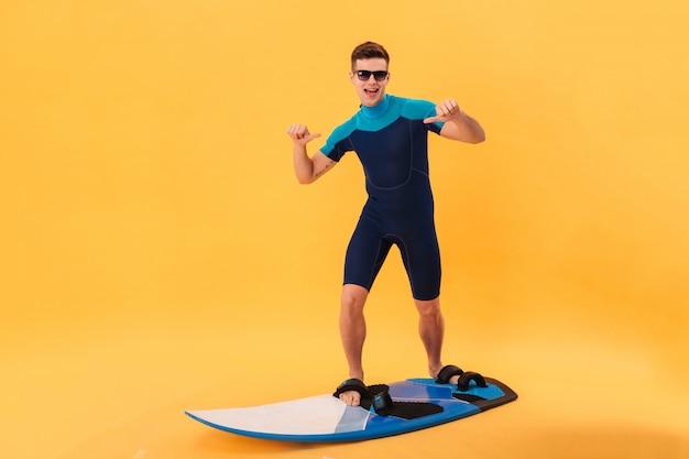Vrolijke surfer in wetsuit en zonnebril met surfboard geeft zichzelf aan en kijkt naar de camera