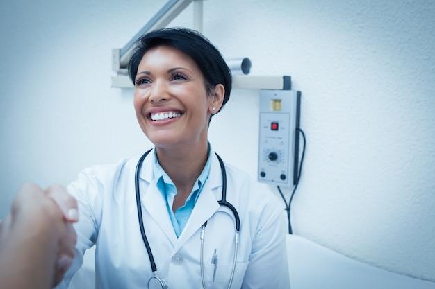 Vrolijke tandarts handen schudden met patiënt