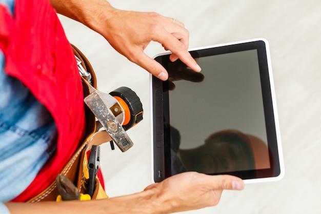 Vrolijke technicus holdong-tablet op wit
