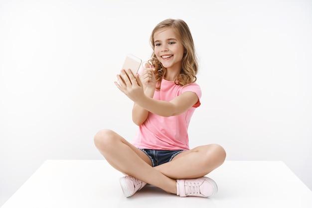 Vrolijke tedere glamour jonge blonde meid praat met moeder via video-oproep, houd smartphone zijwaarts wijzend kijk mobiele telefoon naar voren schattig, neem internetblog op, online stream, pose witte muur