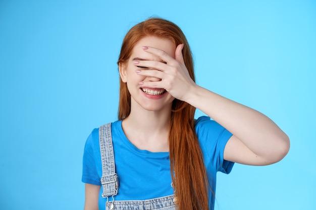 Vrolijke tedere roodharige vriendin voelt zich gelukkig, geniet van zomervakantie, ontspannend vreugdevol weekend, speelse bui, gesloten ogen houden palmgezicht vast, verstoppertje pikaboo-gebaar, staan blauwe achtergrond