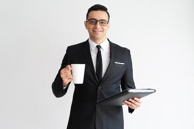 Vrolijke tevreden bedrijfswerknemer die koffie drinkt en met documenten werkt.