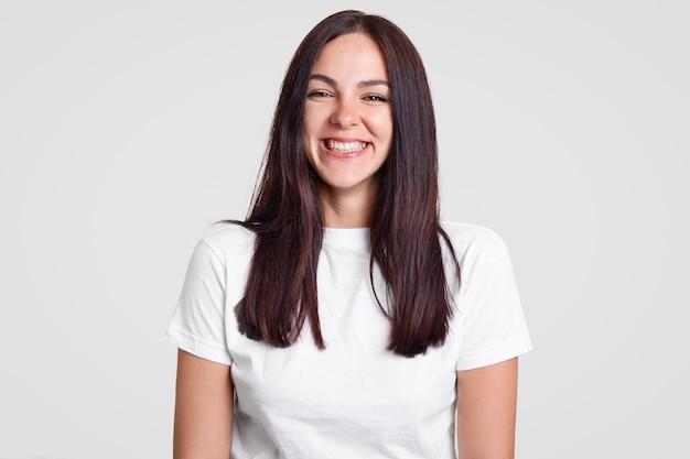 Vrolijke tevreden brunette dame heeft een brede glimlach, een goed humeur drukt positieve emoties uit