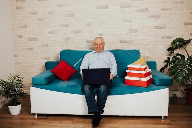 Vrolijke tevreden gepensioneerde volwassen persoon zittend op de bank in de woonkamer bezig met laptop kreeg goed positief nieuws.