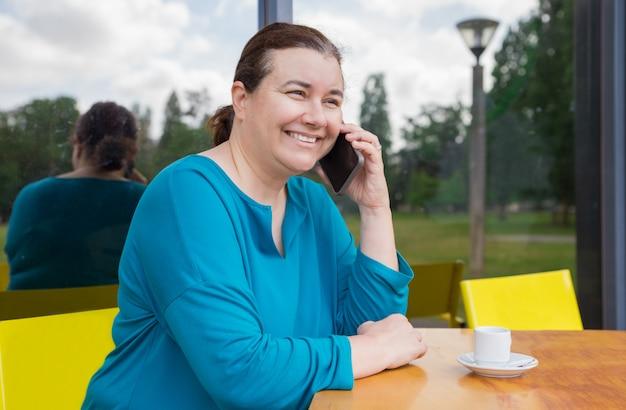 Vrolijke tevreden vrouw die telefoon van gesprek geniet