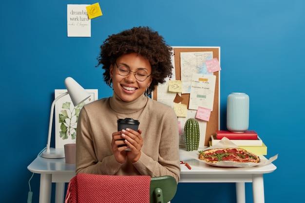Vrolijke tevreden vrouw glimlacht breed, houdt afhaalmaaltijden koffie, draagt bruine trui, vormt tegen werkplek geïsoleerd op blauwe achtergrond