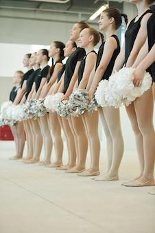 Vrolijke tiener deelnemers van cheerleading competitie met pompons en in de rij staan