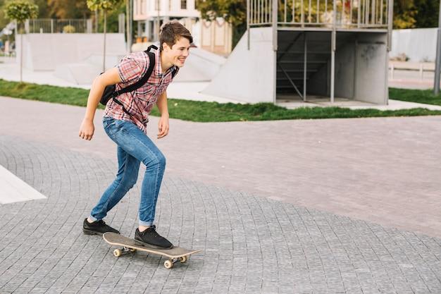 Vrolijke tiener die in park met een skateboard rijden
