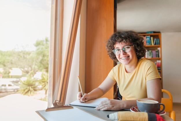 Vrolijke tiener die thuiswerk doen dichtbij venster