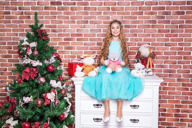 Vrolijke tiener langharige blonde zit op een wit nachtkastje in de buurt van kerstboom, brede glimlach en camera kijken. studio opname