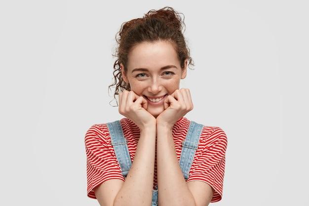 Vrolijke tiener met sproeten houdt de handen onder de kin, grijnst naar de camera, heeft een zachte glimlach