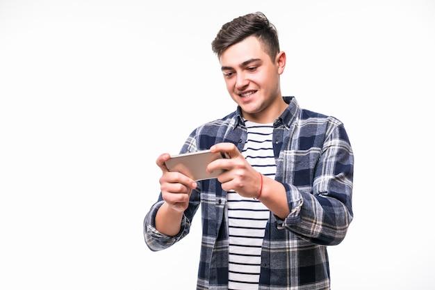 Vrolijke tiener spelen op zijn mobiele telefoon
