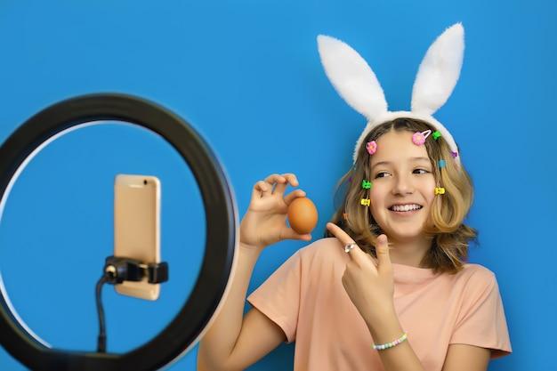Vrolijke tienermeisje blogger met konijnenoren op hoofd houdt een ei in haar handen en voert een online uitzending uit op haar smartphone