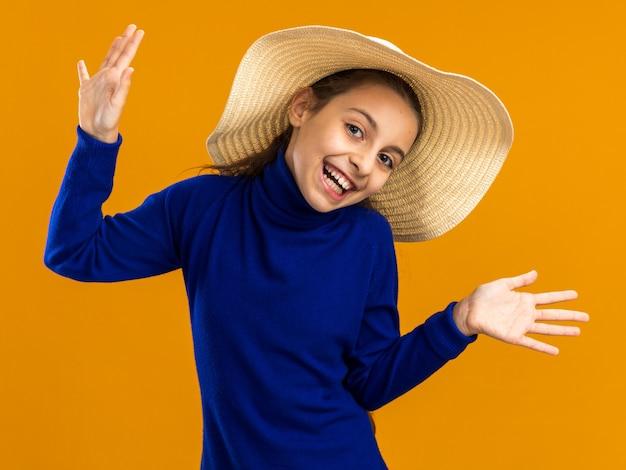 Vrolijke tienermeisje met een strandhoed die naar de voorkant kijkt en lege handen toont die op een oranje muur zijn geïsoleerd