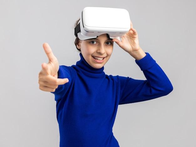 Vrolijke tienermeisje met een vr-headset die het opheft en naar de voorkant wijst, geïsoleerd op een witte muur