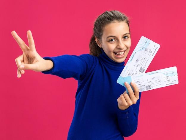 Vrolijke tienermeisje met vliegtuigkaartjes kijkend naar de voorkant doen vredesteken geïsoleerd op roze muur Premium Foto