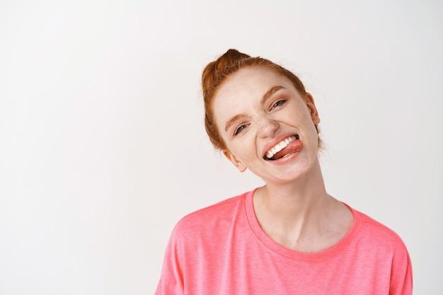 Vrolijke tienervrouw met gemberhaar gekamd in rommelige knot, met witte glimlach en tong, staande tegen witte muur in roze t-shirt