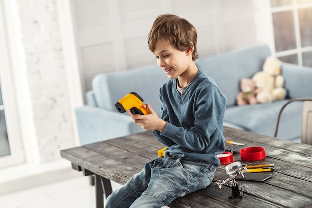 Vrolijke tijd. aantrekkelijke waakzame blonde jongen die lacht en een instrument vasthoudt terwijl hij op de tafel zit