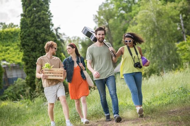 Vrolijke tijd. jonge gelukkige jongens met schattige meisjes arm in arm wandelen op picknick in groen park op zonnige warme dag