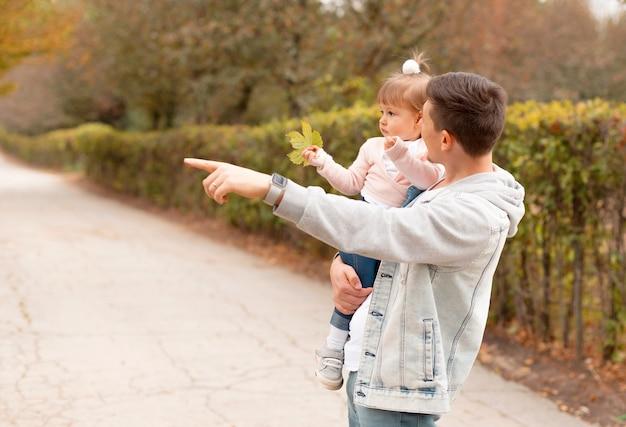 Vrolijke tijd vader en dochter kijken naar iets in de natuur buiten