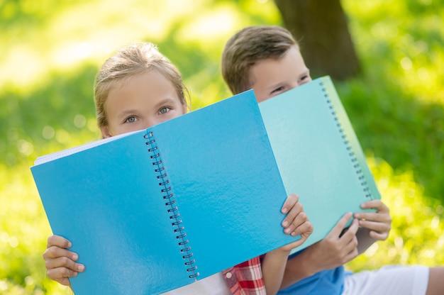Vrolijke tijd. vrolijk meisje en jongen van basisschoolleeftijd in speelse bui verstopt achter lichtblauwe notitieboekjes in het park op mooie dag