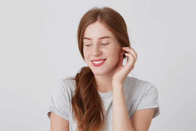 Vrolijke timide jonge vrouw met rood haar en sproeten draagt een grijze t-shirt glimlachend en naar beneden te kijken